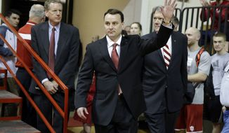 New Indiana NCAA college basketball coach Archie Miller waves as he walks on to the court of Assembly Hall before he was introduced during a news conference on the court in Bloomington, Ind., Monday, March 27, 2017. Miller was the head coach at Dayton. (AP Photo/Michael Conroy)