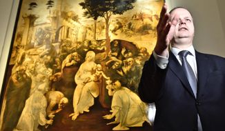 """Uffizi museum manager Erik Smith gestures as Leonardo da Vinci's """"Adoration of the Three Wise Men"""" is returned to the public after 6 years of study and restoration, in Florence, Italy, Monday, March 27, 2017. Painted in 1481, it is one of the most important works of the early Leonardo. (Maurizio Degl' Innocenti/ANSA via AP)"""