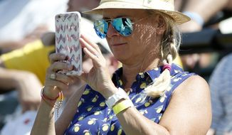 A tennis fan takes a photo during player introductions before a tennis match between Roger Federer, of Switzerland, and Juan Martin del Potro, of Argentina, at the Miami Open, Monday, March 27, 2017 in Key Biscayne, Fla. (AP Photo/Wilfredo Lee)