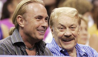 FILE - In this Aug. 23, 2005 file photo, Los Angeles Sparks owner Jerry Buss, right, and his son Johnny Buss watch a WNBA game against the Minnesota Lynx in Los Angeles, Calif. A battle over control of the Los Angeles Lakers among the late Jerry Buss's children is over after an agreement was reached to have Jeanie Buss serve as controlling owner of the storied NBA basketball franchise. Documents filed Monday, March 27, 2017 in Los Angeles Superior Court state that Jim and Johnny Buss have agreed that their sister will serve as the controlling owner for the rest of her life. (AP Photo/Chris Carlson, File)