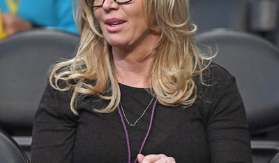 FILE - In this March 3, 2017 file photo, Los Angeles Lakers president Jeanie Buss sits in the stands prior to an NBA basketball game between the Lakers and the Boston Celtics in Los Angeles. A battle over control of the Lakers is over after an agreement was reached to have Jeanie Buss serve as controlling owner of the storied NBA franchise. Documents filed Monday, March 27, 2017 in Los Angeles Superior Court state that Jim and Johnny Buss have agreed that their sister will serve as the controlling owner for the rest of her life. (AP Photo/Mark J. Terrill, File)