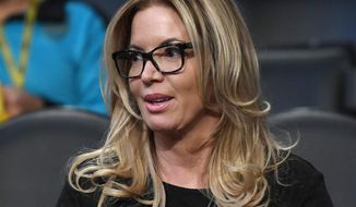 FILE - In this March 3, 2017, file photo, Los Angeles Lakers president Jeanie Buss sits in the stands prior to an NBA basketball game between the Lakers and the Boston Celtics, in Los Angeles. A battle over control of the Lakers is over after an agreement was reached to have Jeanie Buss serve as controlling owner of the storied NBA franchise. Documents filed Monday, March 27, 2017,  in Los Angeles Superior Court state that Jim and Johnny Buss have agreed that their sister will serve as the controlling owner for the rest of her life. (AP Photo/Mark J. Terrill, File)