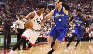 Toronto Raptors guard DeMar DeRozan (10) drives past Orlando Magic centre Nikola Vucevic (9) during first half NBA basketball action in Toronto on Monday, March 27, 2017. (Frank Gunn/The Canadian Press via AP)