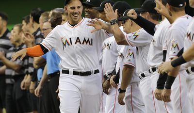 FILE - In this April 5, 2016, file photo, Miami Marlins starting pitcher Jose Fernandez greets his teammates during a ceremony before an interleague opening day baseball game between the Miami Marlins and the Detroit Tigers, in Miami. The Miami Marlins begin their 25th season without their late ace, his legacy badly tarnished by recently disclosed details of his death, which somehow makes the shadow over the franchise even darker.(AP Photo/Alan Diaz, File)