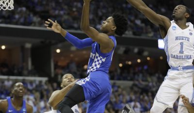 Kentucky guard De'Aaron Fox (0) shoots against North Carolina forward Theo Pinson (1) in the first half of the South Regional final game in the NCAA college basketball tournament Sunday, March 26, 2017, in Memphis, Tenn. (AP Photo/Mark Humphrey)