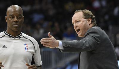 Atlanta Hawks head coach Mike Budenholzer, right, argues a call with official Haywoode Workman during the first half of an NBA basketball game against the Brooklyn Nets, Sunday, March 26, 2017, in Atlanta.(AP Photo/John Amis)