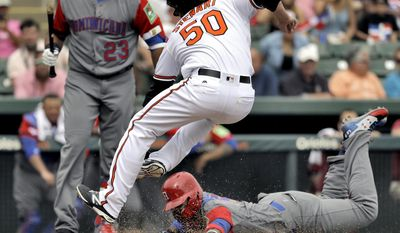 FILE - In this March 7, 2017, file photo, Baltimore Orioles pitcher Zach Stewart (50) goes airborne as he attempts to tag out Dominican Republic infielder Jonathan Villar, who plays for the Milwaukee Brewers, at home plate during the sixth inning of an exhibition baseball game in Sarasota, Fla. Villar scored on a wild pitch by Stewart. Villar seems like he is always on the move for the Brewers. He led the majors in steals last season. He started at shortstop before shifting over to third to make way for heralded prospect Orlando Arcia. Finally, Villar appears to have finally settled on a new home this spring at second base. (AP Photo/Chris O'Meara, File)