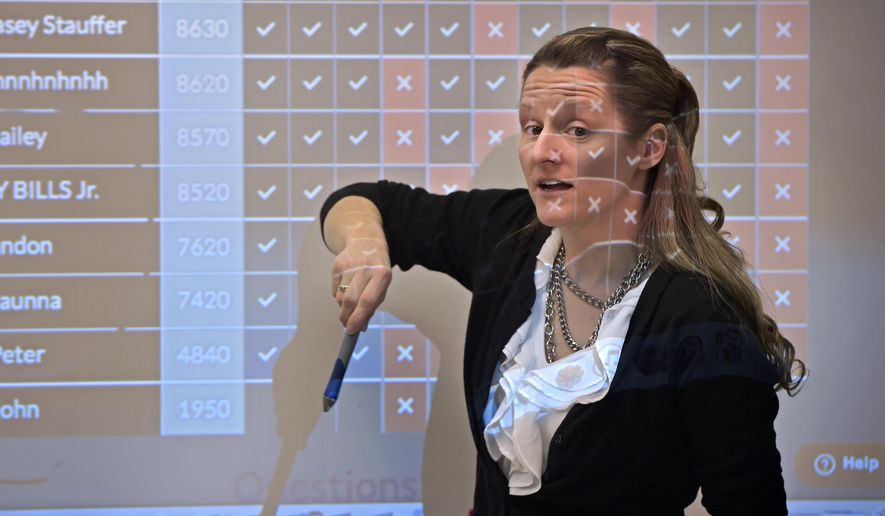 In a Feb. 16, 2017 photo, teacher Kate Stoltzfus stands in a projector light during her algebra class at Pequea Valley High Schoo in Kinzers, Pa. The district is having success with its personalized learning approach to education. (Dan Marschka/LNP via AP)