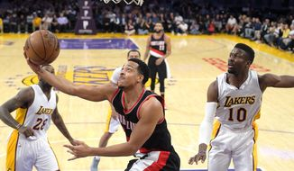 Portland Trail Blazers guard CJ McCollum, center, shoots as Los Angeles Lakers center Tarik Black, left, and guard David Nwaba defend during the first half of an NBA basketball game, Sunday, March 26, 2017, in Los Angeles. (AP Photo/Mark J. Terrill)