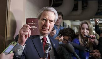 Rep. Walter B. Jones, R-N.C., holds up a copy of the Constitution while talking to reporters as House Republicans emerge from a closed-door meeting on how to deal with the impasse over the Homeland Security budget, at the Capitol in Washington, Thursday, Feb. 26, 2015.  GOP lawmakers have been trying to block President Barack Obama's executive actions on immigration through the funding for the DHS which expires Friday night. Sounding retreat, House Republicans agreed Thursday night to push short-term funding to prevent a partial shutdown at the Department of Homeland Security while leaving in place Obama administration immigration policies they have vowed to repeal.   (AP Photo/J. Scott Applewhite)