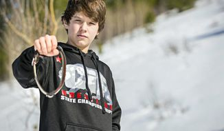 In this March 17, 2017 photo, Canyon Mansfield, 14, holds the collar of his dog, Casey, who was killed March 16 by a cyanide-ejecting device placed on public land near his Pocatello, Idaho, home by federal workers to kill coyotes. The cyanide device, called an M-44, is spring-activated and shoots poison that is meant to kill predators. The U.S. Department of Agriculture in November said it would not put the devices on public land in Idaho. (Jordon Beesley/Idaho State Journal via AP)