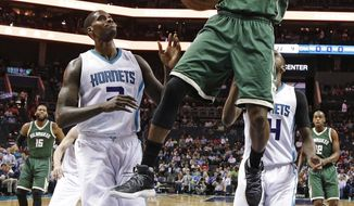Milwaukee Bucks' Tony Snell (21) dunks over Charlotte Hornets' Marvin Williams (2) in the first half of an NBA basketball game in Charlotte, N.C., Tuesday, March 28, 2017. (AP Photo/Chuck Burton)