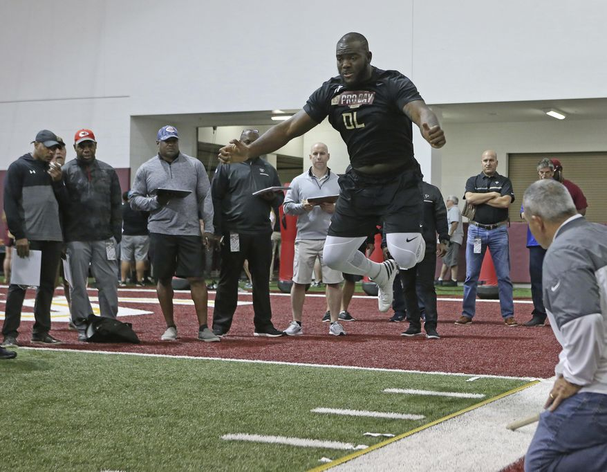 Roderick Johnson performs the standing broad jump drill for NFL scouts during Florida State's pro day, Tuesday, March 28, 2017 in Tallahassee, Fla. (AP Photo/Steve Cannon)