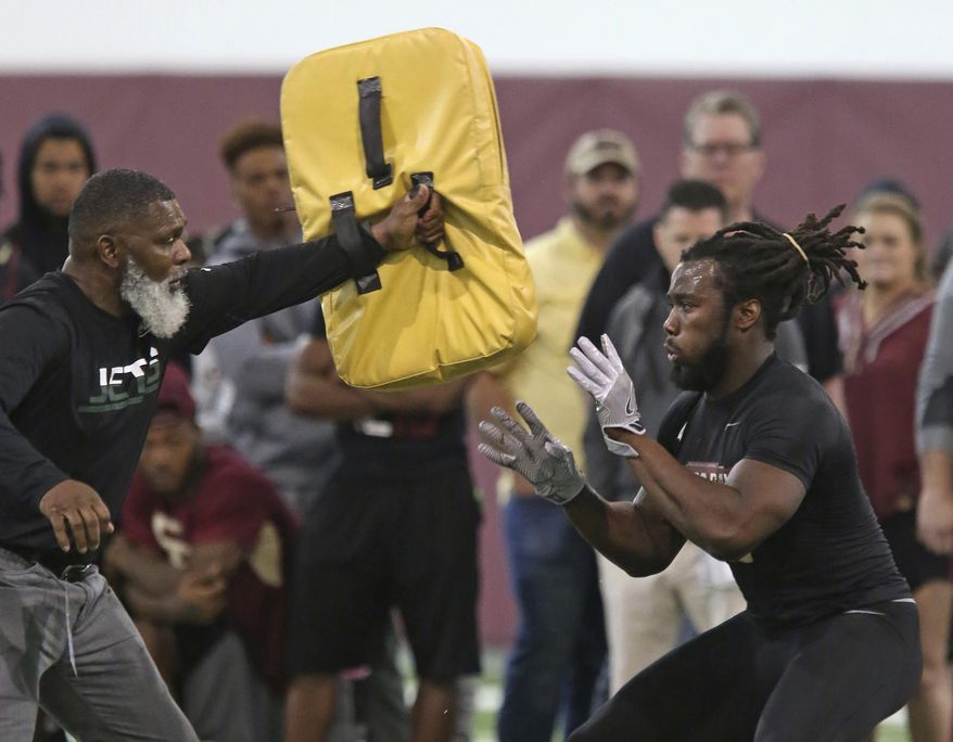 Dalvin Cook, right, works on a drill with an NFL scout during Florida State's pro day, Tuesday, March 28, 2017 in Tallahassee, Fla. (AP Photo/Steve Cannon)