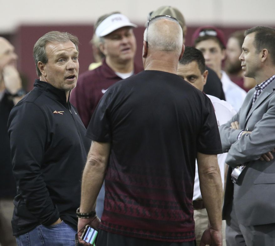 Florida State's head coach Jimbo Fisher, left, talks with NFL scouts during Florida State's pro day, Tuesday, March 28, 2017 in Tallahassee, Fla. (AP Photo/Steve Cannon)