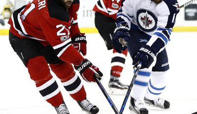 New Jersey Devils right wing Kyle Palmieri (21) and Winnipeg Jets center Bryan Little (18) compete for the puck during the first period of an NHL game, Tuesday, March 28, 2017, in Newark, N.J. (AP Photo/Julio Cortez)