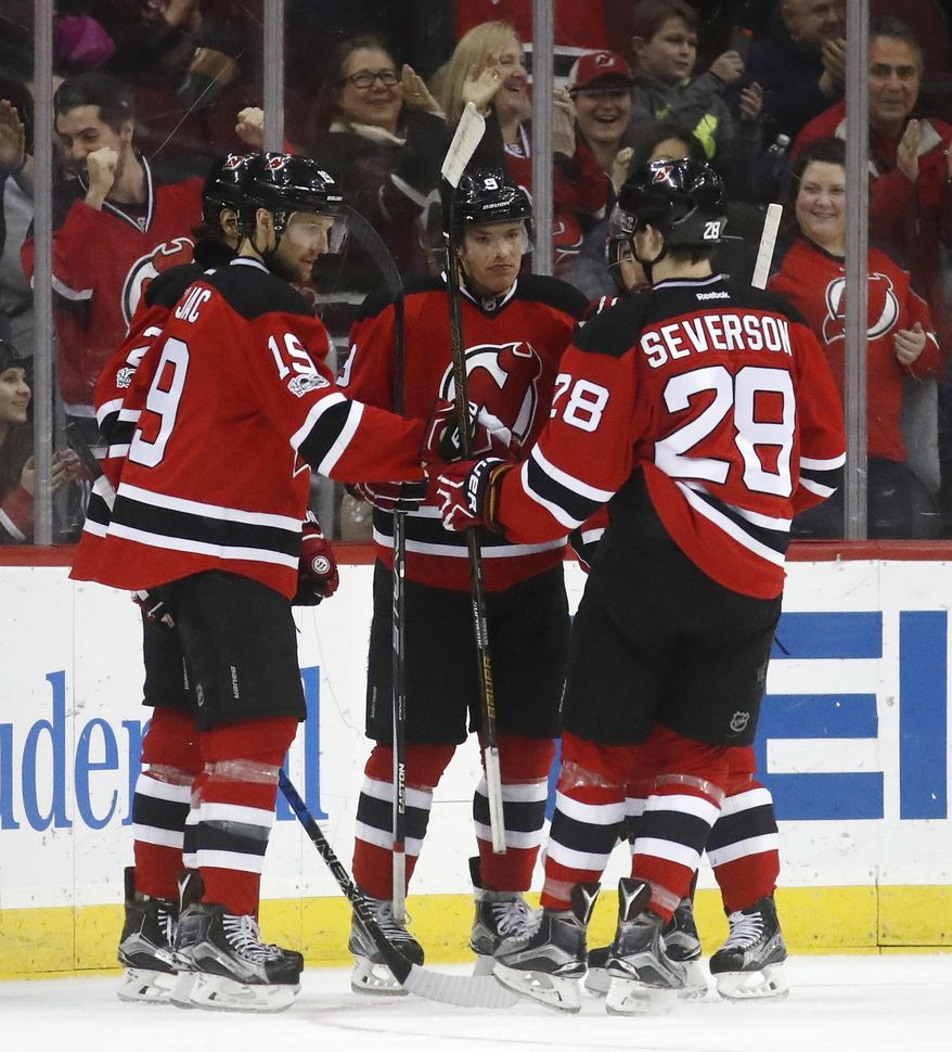 New Jersey Devils players celebrate a goal by Taylor Hall, center, during the first period of an NHL game against the Winnipeg Jets, Tuesday, March 28, 2017, in Newark, N.J. (AP Photo/Julio Cortez)