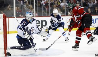 New Jersey Devils right wing Stefan Noesen, right, scores a goal on Winnipeg Jets goalie Connor Hellebuyck (37) during the second period of an NHL game, Tuesday, March 28, 2017, in Newark, N.J. (AP Photo/Julio Cortez)
