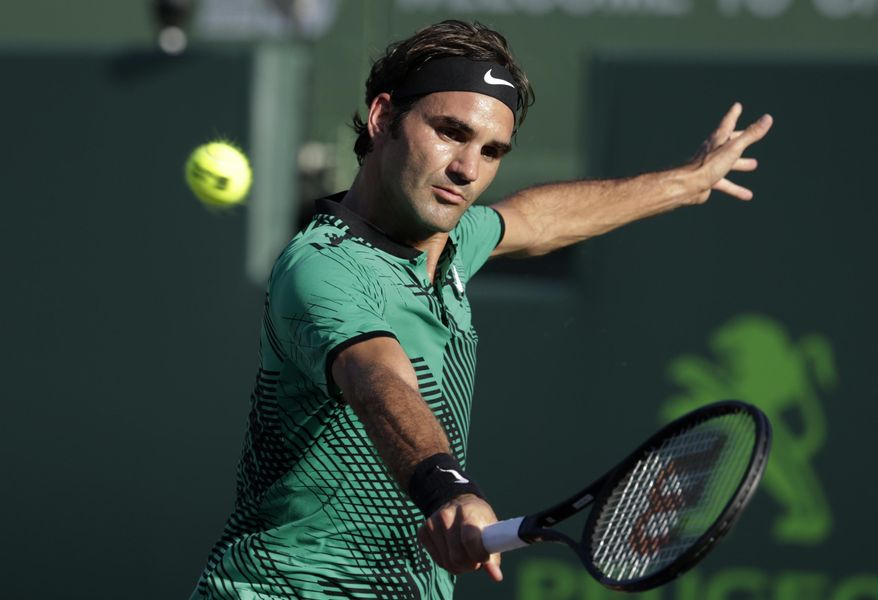 Roger Federer, of Switzerland, hits a return to Roberto Bautista Agut, of Spain, during the Miami Open tennis tournament, Tuesday, March 28, 2017, in Key Biscayne, Fla. (AP Photo/Lynne Sladky)