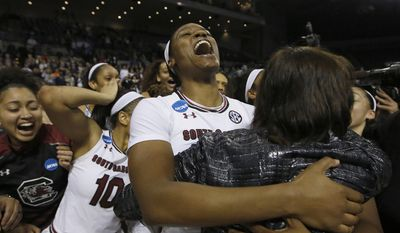 South Carolina's Kaela Davis, center, hugs associate head coach Lisa Boyer, right, in celebration after defeating Florida State, 71-64, in a regional final game of the women's NCAA college basketball tournament, Monday, March 27, 2017, in Stockton, Calif. (AP Photo/Rich Pedroncelli)