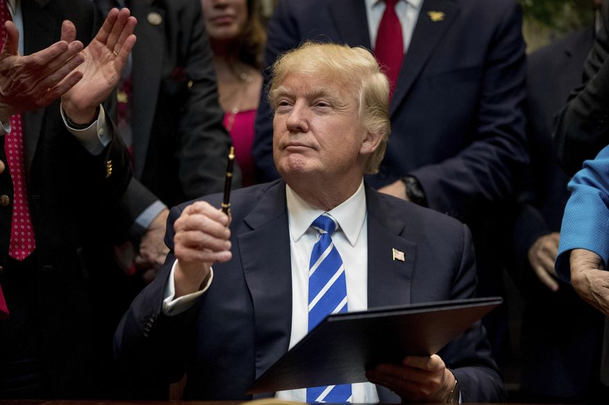 "In this Monday, March 27, 2017, file photo, President Donald Trump holds up a pen he used to sign one of various bills in the Roosevelt Room of the White House in Washington. Ignoring fresh threats from the White House, city leaders across the U.S. are vowing to intensify their fight against Trump's promised crackdown on so-called ""sanctuary cities"" despite the financial risks. (AP Photo/Andrew Harnik, File)"