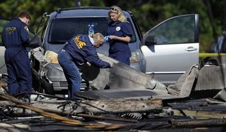 FILE - In this Oct. 12, 2016 file photo, investigators look at the remains of a small plane along Main Street in East Hartford, Conn. Police say the student pilot of the small plane, which crashed on Oct. 11, near the Connecticut headquarters of a military jet engine manufacturer, fought with his instructor and probably crashed deliberately. East Hartford police reports disclosed Tuesday, March 28, 2017, support media stories from months ago. (AP Photo/Jessica Hill, File)