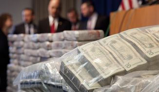 Sacks of money, right, worth $2 million, and 154 pounds of heroin, left, worth at least $50 million, are displayed at a Drug Enforcement Administration news conference, Tuesday, May 19, 2015 in New York. The DEA called the heroin seizure its largest ever in New York state. Officials said on Tuesday that most of the drugs were found in an SUV in the Bronx following a wiretap investigation. (AP Photo/Mark Lennihan) ** FILE **
