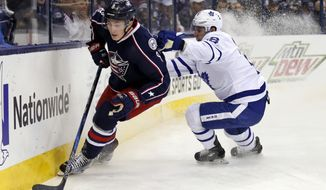FILE - In this Wednesday, March 22, 2017, file photo, Columbus Blue Jackets defenseman Zach Werenski, left, controls the puck against Toronto Maple Leafs forward Mitchell Marner during the first period of an NHL hockey game in Columbus, Ohio. Youth along the blue line will be served this postseason. Werenski and teammate Seth Jones are among more than two-dozen defensemen under the age of 24 filling prominent roles. (AP Photo/Paul Vernon, File)
