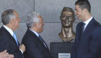 Portuguese president Marcelo Rebelo de Sousa, left, Portuguese Prime Minister Antonio Costa, 2nd left and Real Madrid's Cristiano Ronaldo stand next to a bust of the player at the Madeira international airport outside Funchal, the capital of Madeira island, Portugal, Wednesday March 29, 2017. Madeira International Airport has been renamed after local soccer star Cristiano Ronaldo on Wednesday during a ceremony, with family, at the airport outside his Funchal hometown. (AP Photo/Armando Franca)