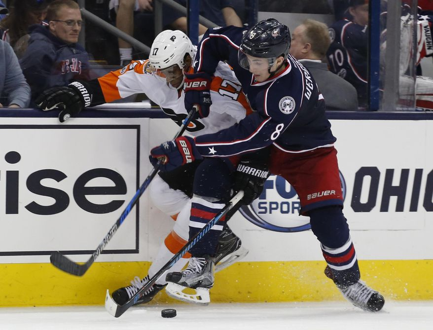 Philadelphia Flyers' Wayne Simmonds, left, and Columbus Blue Jackets' Zach Werenski fight for a loose puck during the third period of an NHL hockey game Saturday, March 25, 2017, in Columbus, Ohio. The Blue Jackets beat the Flyers 1-0. (AP Photo/Jay LaPrete)