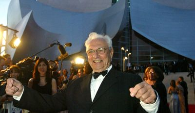 FILE - In this Oct. 23, 2003, file photo, building architect Frank Gehry takes the pose of a symphony conductor as he arrives for a grand opening concert gala at the Walt Disney Concert Hall in Los Angeles. The Getty Research Institute announced Wednesday, March 29, 2017, that it has acquired archives containing hundreds of thousands of sketches, drawings, models, photographs, slides and paperwork involving projects that Gehry designed between 1954 and 1988. (AP Photo/Kevork Djansezian, File)
