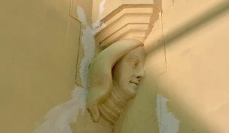 In this undated photo provided by St. Mary's Church, the carved figure of a woman's face is visible on a wall in the church in Newport, R.I. The figure was discovered after a large organ was moved during restoration of the church where John F. Kennedy and Jacqueline Bouvier got married in 1953. (Cody Mead/St. Mary's Church via AP)