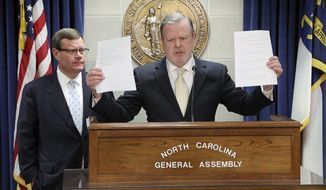 Republican leaders Rep. Tim Moore, left, and Sen. Phil Berger, hold a news conference Tuesday, March 28, 2017, in Raleigh, N.C., where they announced they thought they had reached a compromise with Democratic Gov. Roy Cooper on a replacement for HB2. Berger holds papers that he said were the Governor's proposal. The law limits LGBT nondiscrimination protections and requires transgender people to use public restrooms corresponding to the sex on their birth certificate.  (Chris Seward/The News & Observer via AP)