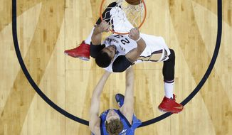New Orleans Pelicans forward Anthony Davis (23) slam dunks ahead of Dallas Mavericks forward Dirk Nowitzki (41) in the first half of an NBA basketball game in New Orleans, Wednesday, March 29, 2017. (AP Photo/Gerald Herbert)