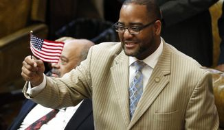 Rep. Orlando Paden, D-Clarksdale, waves a small American flag as the Mississippi Legislature ended its 2017 regular session Wednesday, March 29, 2017, at the Capitol in Jackson, Miss. However lawmakers will have to return later to pass budgets for the attorney general's office and the Department of Transportation. (AP Photo/Rogelio V. Solis)