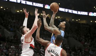 Denver Nuggets forward Wilson Chandler shoots the ball over Portland Trail Blazers center Jusuf Nurkic, left, and Portland Trail Blazers forward Maurice Harkless, right, during the first half of an NBA basketball game in Portland, Ore., Tuesday, March 28, 2017. (AP Photo/Steve Dykes)