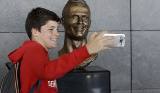 A boy takes a selfie next to the bust of Cristiano Ronaldo at the Madeira international airport outside Funchal, the capital of Madeira island, Portugal, Wednesday March 29, 2017. Madeira International Airport has been renamed after local soccer star Cristiano Ronaldo on Wednesday during a ceremony, with family, at the airport outside his Funchal hometown. (AP Photo/Armando Franca)