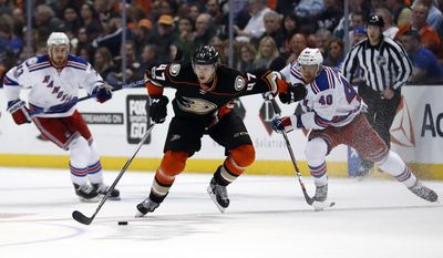 Anaheim Ducks defenseman Hampus Lindholm, center, of Sweden, races against New York Rangers right wing Michael Grabner, right, of Austria, for the puck during the second period of an NHL hockey game, Sunday, March 26, 2017, in Anaheim, Calif. (AP Photo/Ryan Kang)