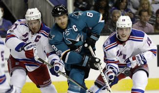 San Jose Sharks' Joe Pavelski (8) is defended by New York Rangers defenseman Ryan McDonagh, left, and Jesper Fast (19) during the second period of an NHL hockey game Tuesday, March 28, 2017, in San Jose, Calif. (AP Photo/Marcio Jose Sanchez)
