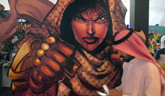 FILE - In this Friday, Feb. 17, 2017, file photo, a visitor walks past a banner showing Latifa, Saudi super woman character, during the Saudi Comic Con (SCC) which is the first event of its kind to be held in Jiddah, Saudi Arabia. The kingdom, which bans movie theaters and other entertainment venues, is challenging its ultraconservative image and loosening the reins on fun by opening its doors to live shows, including some American ones. (AP Photo, File)