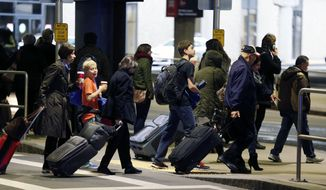 In this Nov. 26, 2014, file photo, passengers leave a departure area after arriving at Logan International Airport in Boston. (AP Photo/Michael Dwyer, File)