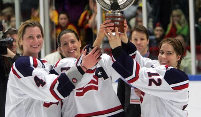 FILE - In this April 9, 2005, file photo, U.S. team members, from left, Angela Ruggiero, Cammi Granato and Jenny Potter hold the trophy after winning the the Women's World Ice Hockey Championship in the Cloetta Center in Linkoping, Sweden. Granato's biggest victory in hockey came 12 years after she retired. When USA Hockey and the women's national team agreed to a contract that ended a wage dispute, Granato couldn't put her happiness into words. (Jonas Ekstromer/Pressens Bild via AP, File)
