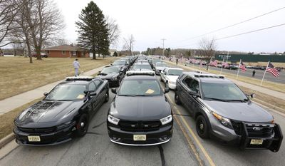 Law enforcement vehicles and flags line a road during the visitation and funeral procession for Everest Metro Police Detective Jason Weiland on Wednesday, March 29, 2017, in Weston, Wis. Weiland was killed in the line of duty during a string of deadly shootings in Rothschild on March 22, 2017, that left three others dead. (T'xer Zhon Kha/The Post-Crescent via AP)