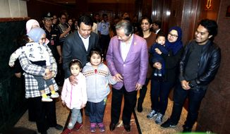 Malaysia's Foreign minister Anifah Aman, third right, walks next to the nine Malaysians who were returned from Pyongyang at Kuala Lumpur International airport in Sepang, Malaysia, Friday, March 31, 2017. Malaysia said Thursday it has agreed to release the body of Kim Jong-nam to North Korea in exchange for the return of nine Malaysians held in the North's capital. (AP Photo/Daniel Chan)