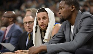Golden State Warriors guard Stephen Curry, left, talks to Warriors forward Kevin Durant during the first half of an NBA basketball game against the San Antonio Spurs, Wednesday, March 29, 2017, in San Antonio. Golden State won 110-98. (AP Photo/Darren Abate)