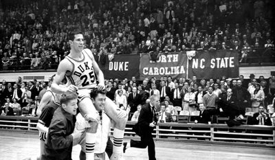 FILE - In this 1963 photo, Duke basketball player Art Heyman (25) is carried by teammates in Durham, N.C. (The Herald-Sun via AP, File)