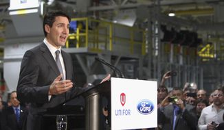 Canada's Prime Minister Justin Trudeau speaks at the Ford Essex Engine Plant in Windsor, Ontario, Canada, on Thursday, March 30, 2017. Ford Motor Co. is hiring more than 300 engineers for a new connected-vehicle research center in Ottawa, Ontario, the automaker said Thursday. (Dave Chidley/The Canadian Press via AP)
