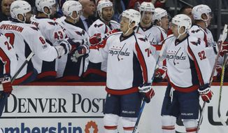 Washington Capitals defenseman John Carlson, front left, is congratulated after scoring a goal as he passes the team box with center Evgeny Kuznetsov, of Russia, in the first period of an NHL hockey game against the Colorado Avalanche late Wednesday, March 29, 2017, in Denver. (AP Photo/David Zalubowski))