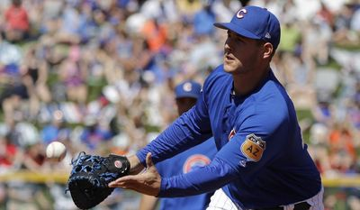 Chicago Cubs' Anthony Rizzo toss the ball to Jake Arrieta during the third inning of a spring training baseball game against the San Francisco Giants, Tuesday, March 28, 2017, in Mesa, Ariz. (AP Photo/Darron Cummings)