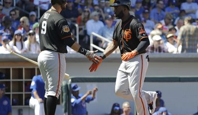 San Francisco Giants' Denard Span is congratulated by Brandon Belt after Span hit a home run during the first inning of a spring training baseball game against the Chicago Cubs, Tuesday, March 28, 2017, in Mesa, Ariz. (AP Photo/Darron Cummings)